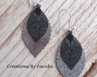 Earrings with shiny filigree silver and black, and a tiny black leaf