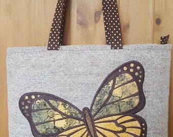 Quilted tote bag with machine embroidered applique design.
