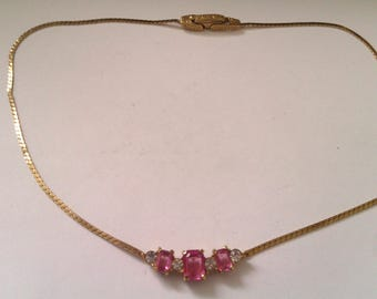gold coloured necklace with pink and clear stones