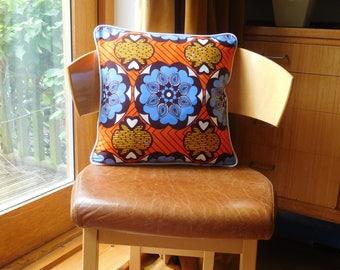 Geometric African wax print cushion in blue, orange and yellow.  Vivid geometric African wax print cushion in blue, orange and yellow.