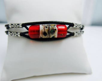 Leather strap and glass beads.