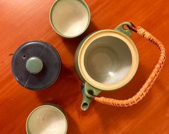Vintage ceramic teapot, wooden handle, and four tea cups