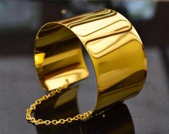 Gold Mirror shine cuff bracelet with chain detail.