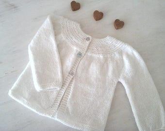 White hand knitted round yoke baby vest/cardigan