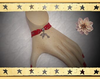Red and beige floral bracelet featuring a leaf and Ladybug pendant