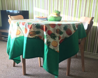 Funky pineapples print cotton green edged tablecloth .