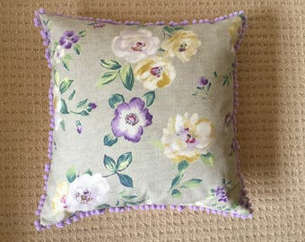 Cushion with pom pom trim detail