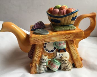 Decorative teapot garden bench with fruit and kittens.