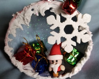 Christmas diorama ornament and polymer clay santa, shiny presents, and jingle bell snowflake