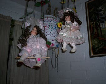 Cute Dolls , some of them on a Swing , other stand up.