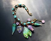 Handmade lampwork glass charm bracelet by Lori Lochner sping green pod and purple blossom artisan boho bronze bracelet.