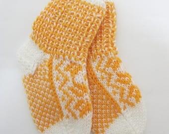 Handknitted baby socks with norwegian pattern