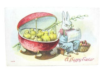 Easter Greeting. Antique Postcard. Bunny Rocking a Cradle of Chicks. Basket of Colored Easter Eggs. 1910s Collectible Holiday Fantasy Card