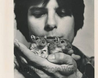 Young man holding two hamsters in hand vintage photo