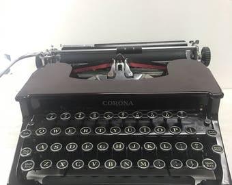 Maroon portable typewriter by smith & corona