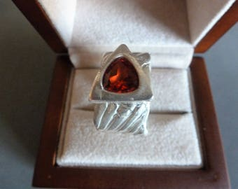 Red Triangle Ring is a thick band of 999 fine silver, herringbone-textured and flashing a large ruby trillion framed in fine silver. Size 8.