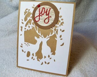 """Merry Christmas wishes card features two deer in the forest, and the word JOY!  Inside reads """"We wish you a Merry Christmas.""""Original design"""