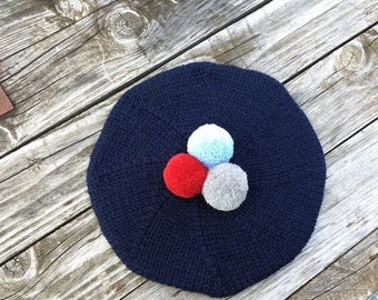 Dark blue beret with pompons.