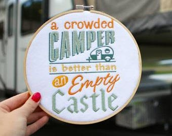 A crowed camper embroidered wall hanging