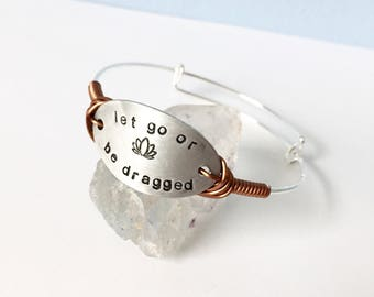 Let go or he dragged adjustable bangle in aluminum, stainless steel and copper