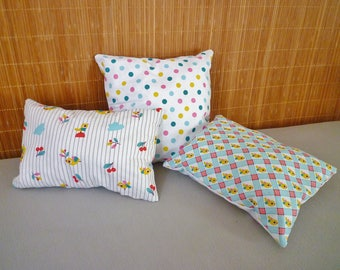 Set of three coordinated cushions and birds motifs and white polka dots, pink, yellow, blue, green, white tones