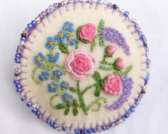 Roses and cottage garden flowers on a near-white felt brooch with beaded border