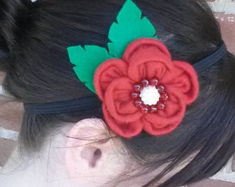 Red felt flower with red and white beading on elastic black headband