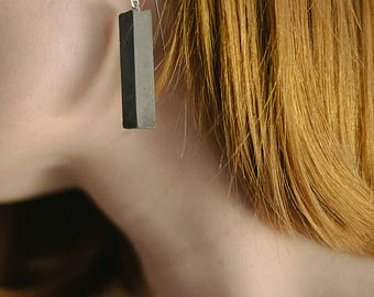 Rectangular concrete pendant on the silver earrings