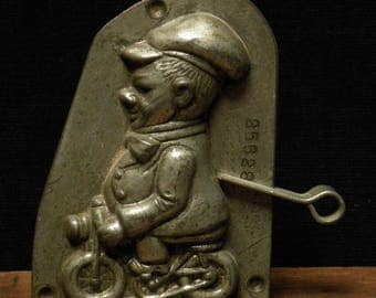 Antique two part chocolate mold of a funny man on a little bicycle  by Anton Reiche.