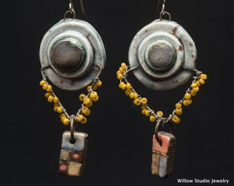 Those Who Carry, circular shields with angled drop wires festooned in mustard yellow seedbeads, small colorful clay pendant dangles below