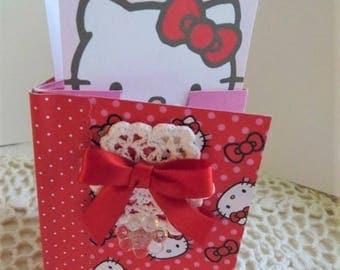 "Hello Kitty mini album (paper) w/ pockets, 3"" x 4 -1/2"" w/ matching gift bag, HK tags, gold bow, red, white, black, 8 pockets, 23 tags."
