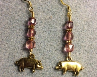 Gold pig charm dangle earrings adorned with pink Czech glass beads.