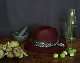 Burgundy fedora hat decorated with a cotton scarf