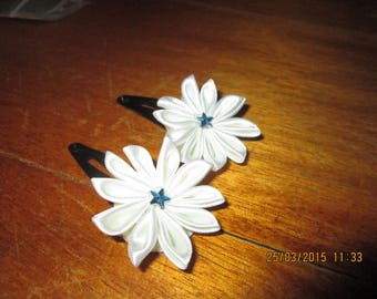 set of two black strips with a white flower and a turquoise star rhinestone