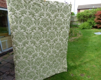 A wholecloth quilt with a green brocade front. Beige/green/. Single bed quilt, double topper, large lap quilt or sofa throw. Handquilted.