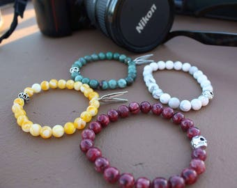 Bead bracelets (honey amber yellow,african jade green, white howlite) 8mm round with silver feather charms or silver skull