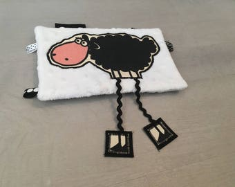 Black and white sheep cuddly with long legs