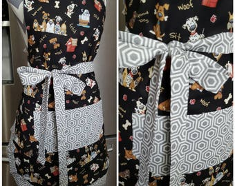 Adult apron. Woman's apron. Black fabric on main with doggies, bones and wording. Gray and white on pocket, ties, and frills.