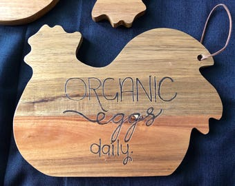 Decorative cutting board in shape of chicken with wood burned phrase organic eggs daily