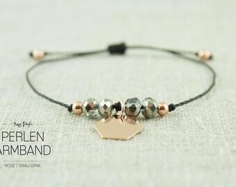 Beaded bracelet grey opaque with brass pendant
