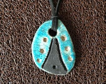 Pendant necklace turquoise and black Raku holes