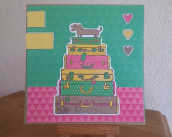 card with dog on a pile of luggage