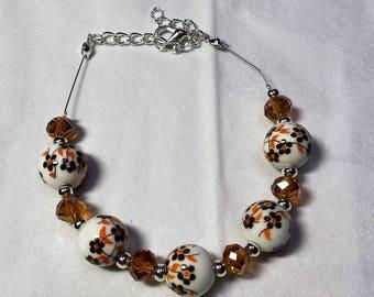 Cable bracelet brown/orange porcelain beads