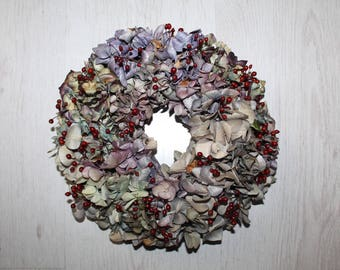 Beautiful hydrangea wreath in blue and violet with small red hips