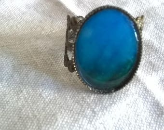 an incredible blue green on the bottom of a resin cabochon bronze ring