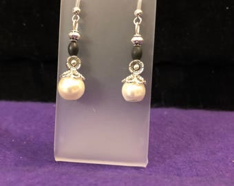 White faux pearl and black drop earrings.