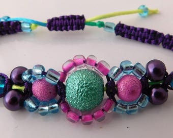 Three textured beads in pink, purple and green on a macrame bracelet