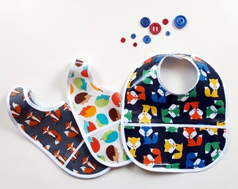 Stained and waterproof laminated cotton bib with pocket. Waterproof laminated cotton bid with pocket