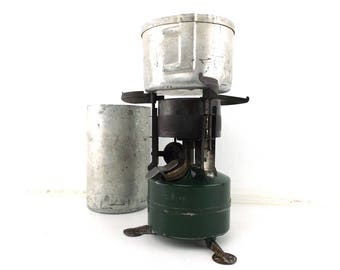 coleman stove. vintage camping. coleman camping stove. camping gear. portable stove. M1950. gas stove. carrying canister. metal pan and cup