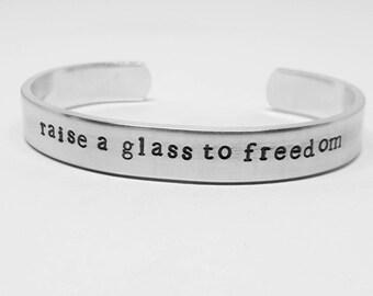 Raise a glass to freedom: Hand Stamped Aluminum Lin-Manuel Miranda Hamilton musical quote cuff by fandomonium